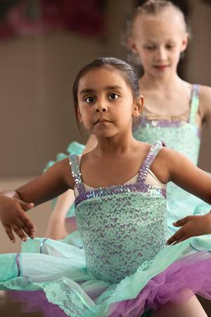 latina girl: Two little girls in ballet dresses practice in a studio
