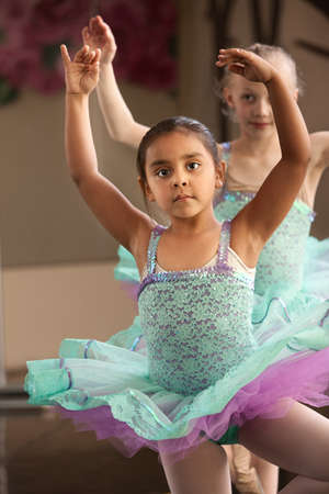 Cute little girls in ballet dresses practice in a studio