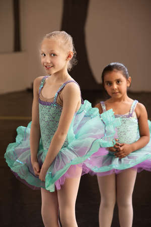 Shy little girls in ballet dresses at a dance studio