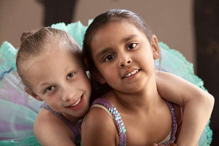 mexican girl: Young ballet student gives her friend a hug