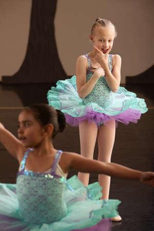 Two little girls in ballet dresses practice in a studio