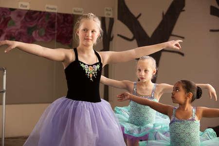 niños bailando: Jóvenes estudiantes de ballet de diferentes edades practicando juntos