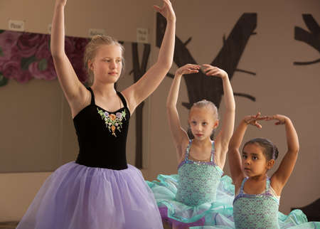 Three female dance students of different ages practicing together photo