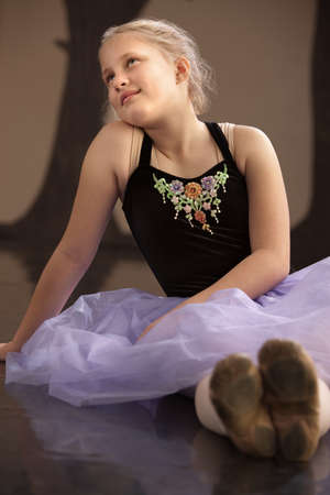 Teen caucasian ballet student sits on the floor photo