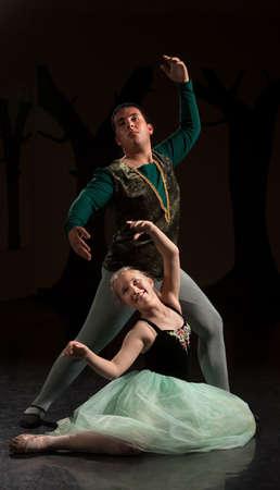ballet hombres: Jóvenes bailarines que realizan sobre fondo oscuro Foto de archivo