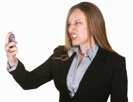 Woman with clenched teeth and telephone over white background photo