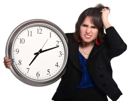 befuddled: Confused businesswoman with clock past seven over white background Stock Photo