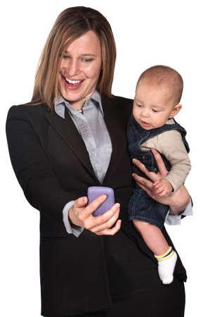 madre trabajando: Mujer bonita con el bebé mirando a la pantalla de su teléfono Foto de archivo