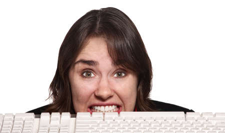 technophobe: Woman with clenched teeth behind computer keyboard Stock Photo