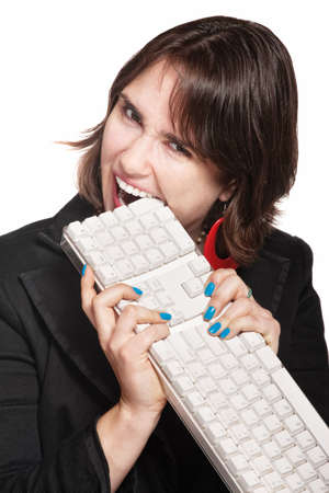 munching: Crazy professional lady gnawing on a computer keyboard Stock Photo