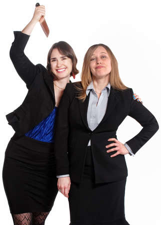 Smiling woman holds a knife behind clueless coworker