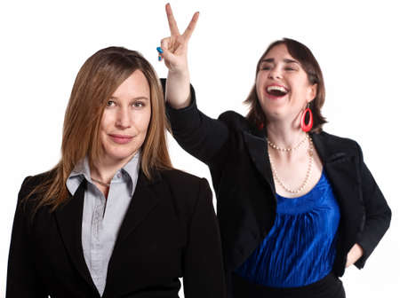 disrespectful: Professional woman holds rabbit ears gesture over a worker Stock Photo