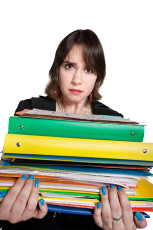 burdened: Overwhelmed young professional holds stack of binders