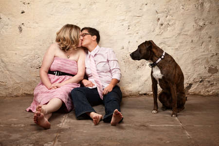 gay couple: Lesbian kissing couple on floor with pet dog watching Stock Photo