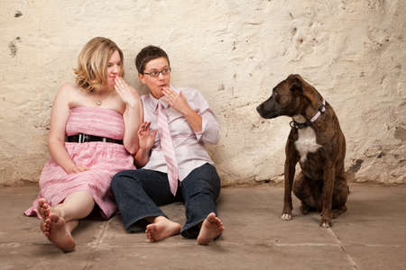 Two surprised ladies on the floor with pet dog photo
