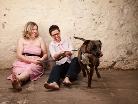 lesbianas: Riendo amigos sentados en el suelo con el perro gracioso Foto de archivo