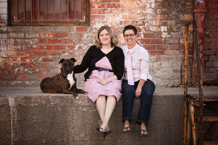 lesbian love: Smiling female friends with dog on old loading dock Stock Photo