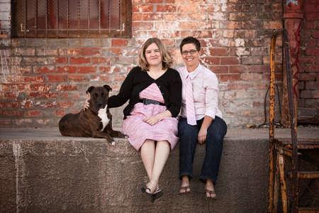 boda gay: Sonriente amigas con el perro en muelle de carga de edad