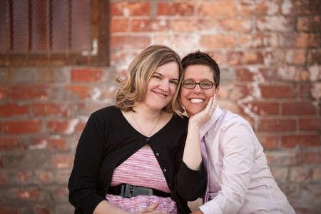 lesbians: Pareja de lesbianas sentados uno junto al otro al aire libre
