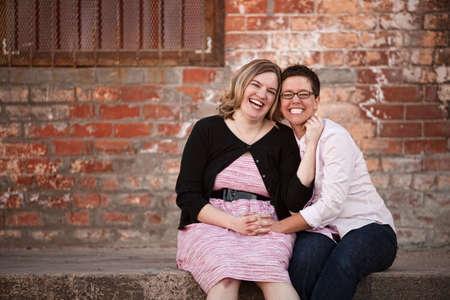 lesbians: Dos amigas sentado fuera en el muelle de carga