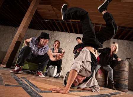 hip hop dance: Young man showing friends freestyle moves on cardboard