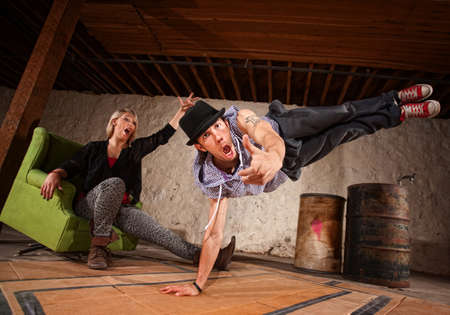 Handsome Latino break dancer in mid air with cheering friend photo