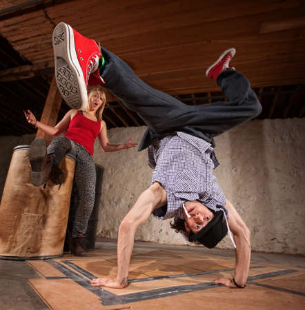 Flexible young Mexican break dancer with impressed friend photo