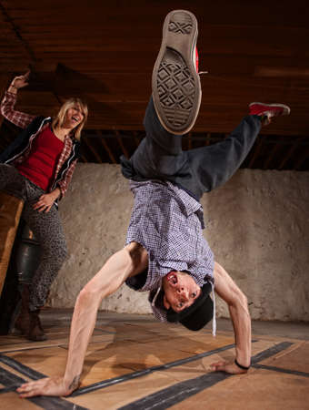 Young woman cheers on man doing freestyle hand stands photo