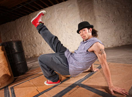 dance floor: Handsome Latino male with leg up while break dancing Stock Photo