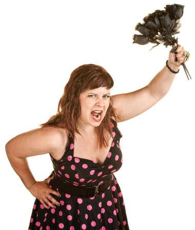 humeur: Femme en col�re dans la robe rose de point de polka tenant des roses noires Banque d'images