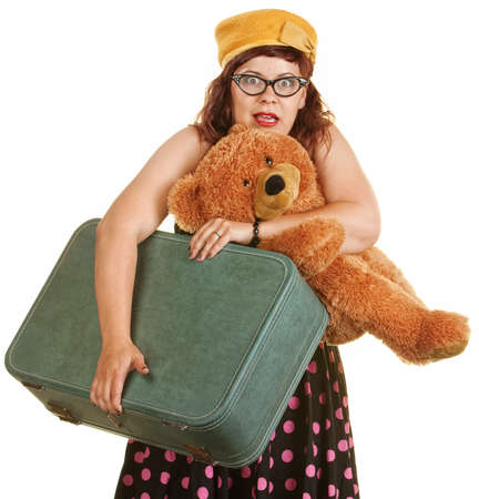 Scared woman in retro style dress with suitcase and teddy bear photo