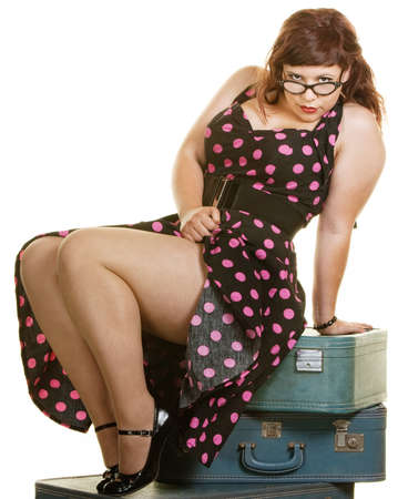 Sexy plus size woman sitting on stack of suitcases photo