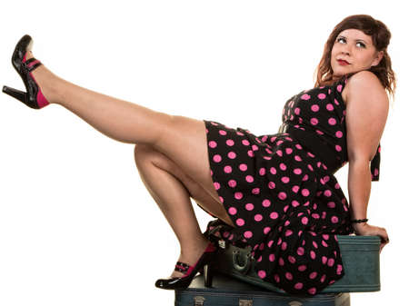 kick off: Flirtacious Caucasian woman on suitcases kicking her leg Stock Photo