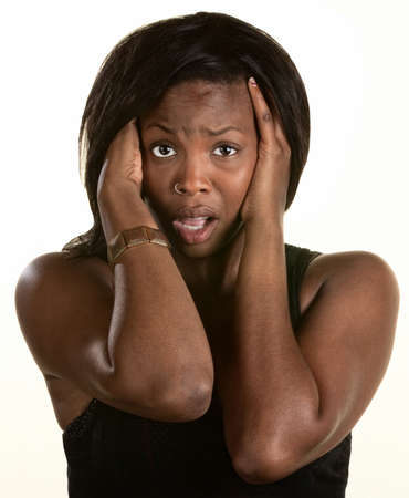 Frightened Black woman with hands on head photo