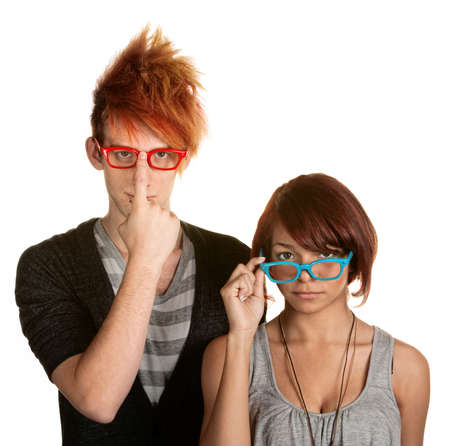Awkward male and female teenager adjusting their glasses