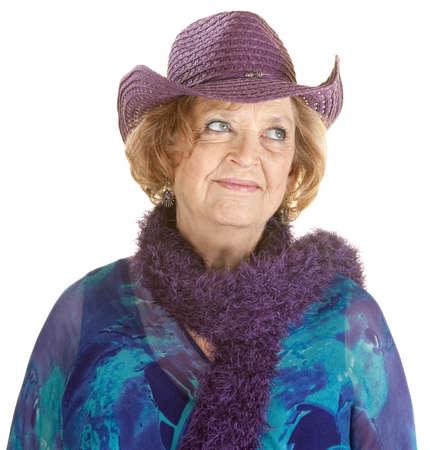 Grinning European senior woman in purple hat photo