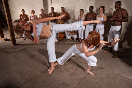 Young woman evades a kick during a Capoeira demonstration photo