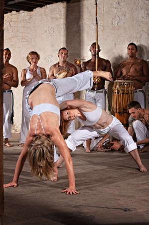 arte marcial: Pareja de mujeres practicantes de capoeira tocando con el grupo