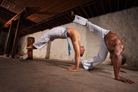 martial arts: Dos expertos masculinos fuertes capoeira lucha interior
