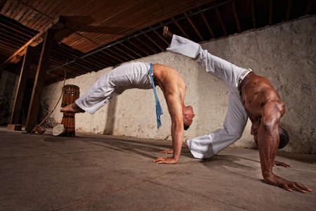 BACKFLIP: Two strong male capoeira experts fighting indoors
