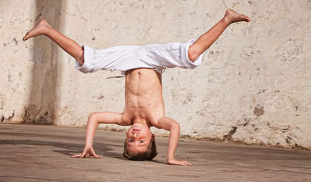 headstand: Young capoeria artist performing a headstand on concrete