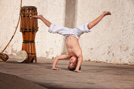 Cute capoeria boy in headstand with African music instruments photo