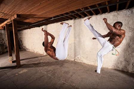 Handsome capoeria martial artists perform flying kicks Stock Photo