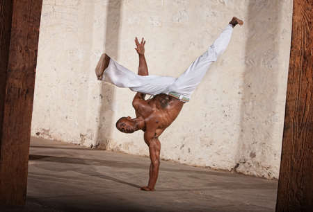 Attractive Brazilian man performing a capoeria kick