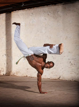 limber: Strong African man demonstrating a Capoeria one armed kick Stock Photo