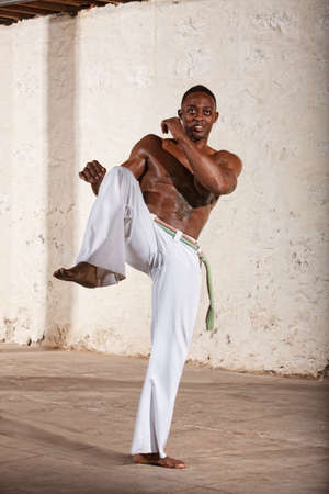 limber: Handsome young Brazilian man doing a Capoeria knee kick