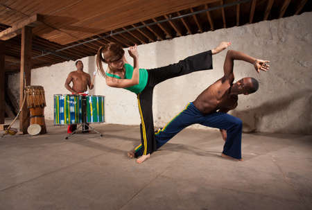 agility people: Caucasian woman throws a capoeria kick with drummer in background Stock Photo