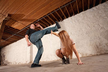 Young woman being kicked by Caucasian male photo