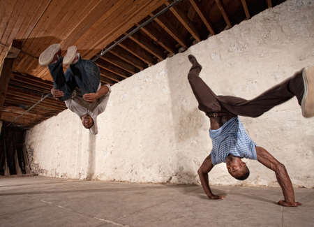 Two acrobatic capoeria artists do headstands and backflips photo
