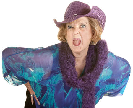 Angry senior woman in hat sticking out her tongue Stock Photo